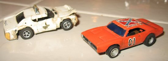 Two Painted AFX slot cars a white sheriff car and an orange General Lee 01 car
