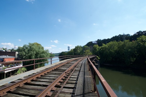 A view across the railroad tracks that go over a river into the woods
