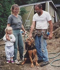 Tracker the Bloodhound sitting in the dirt with a lady, a man and a little girl