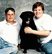 Two boys are sitting around a black Labrador Retriever that is sitting on a backdrop. The dogs mouth is open and it looks like it is smiling