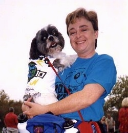 A lady in a blue shirt is holding a black with white Shih Tzu dog against her shoulder. The Shih Tzu and the lady are both looking forward.