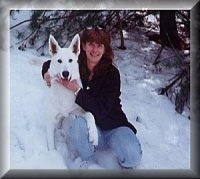 American White Shepherd sitting next to a lady in a snowy terrain posing for a picture