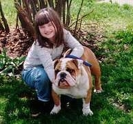 English Bulldog in the yard with her owner kneeling down holding onto her