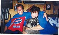 A man has his arm around the shoulder of a lady, who has her arms around a wolf-looking, black, grey with white mixed breed dog. They are both wearing blue sitting on a couch in front of a wood wall in a home. The man has a red and blue sports team pillow on his lap.