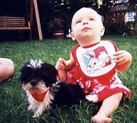 A tiny black with white Shih Tzu puppy is sitting on grass and there is an infant baby in a red dress sitting behind the puppy. The baby is looking up in the air and the pup is looking forward.