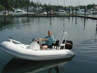 A black Schipperke dog is standing on the back of a boat that is on the water. There is a man sitting in the drivers seat of the boat.