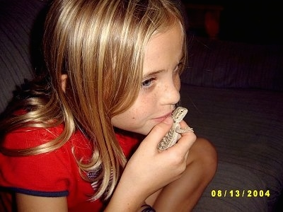 A blonde haired girl has a baby Bearded Dragon in her hand and she is holding it close to her mouth.