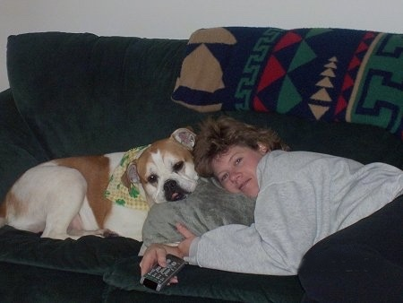 A tan with white Olde English Bulldogge wearing a yellow and green bandana laying on a green couch with its head on a gray pillow. The dog is head to head with a lady in a gray sweatshirt who is also laying on the pillow and holding a TV remote control.