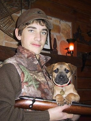 Ace the Black Mouth Cur puppy being held by a male person who is posing with a gun