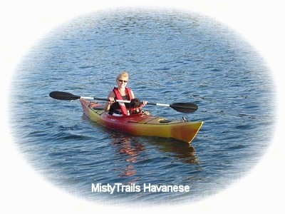 A lady is sitting behind a black with white Havanese in a Kayak out in the middle of open water.