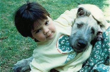 A child has its arm around the head of a white with tan Irish Wolfhound that is laying in grass