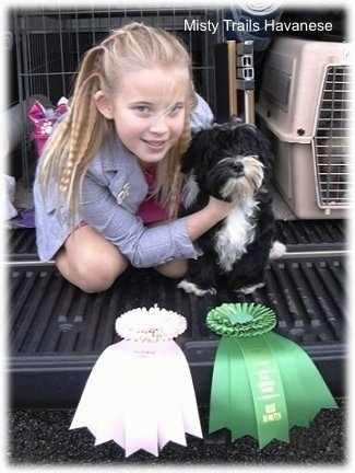A blonde haired girl is sitting on a truck bed holding onto a black and white puppies neck to pose it. They have a pink ribbon and a green ribbon in front of them