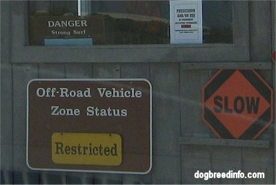 Booth with signs on it 'Off-Road Vehicle szone Status Restricted', 'Slow', 'Danger Strong Surf'