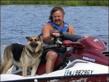 A German Shepherd is riding on a Jet Ski with a Man in a blue life jacket