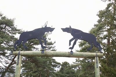 Two iron Wolf silhouettes over a wooden entrance way.