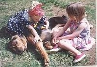 A girl in a blue polka dot dress and a girl in a pink polka dot dress are laying around a black and tan Bloodhound dog sleeping in grass.