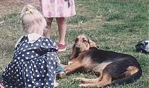 A child in a blue and white polkadot dress is kneeling in front of a black and tan Bloodhound that is laying on its right side. There is another child in a pink polka dot dress behind the dog.