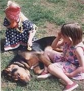 A girl in a blue polka dot dress is putting a Stethoscope on the side of a Bloodhound that is laying in grass. There is a girl in a pink polka dot dress sitting next to the Bloodhound.