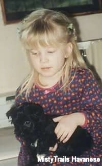 A little blonde haired girl is holding a black with white Havanese puppy in her hands