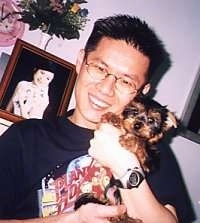 A man is standing next to a framed picture of a lady and he is holding a tiny black and tan Silky Terrier puppy in his arms.