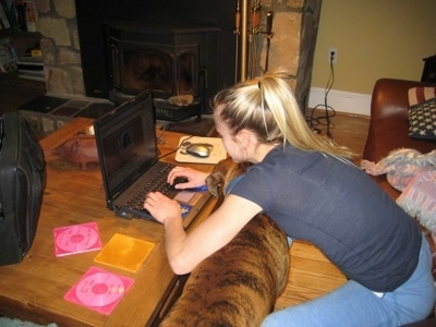 Amie working on HorsesWithAmie.com while Bruno the Boxer squeezes between her arms