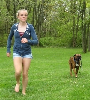 Amie running and Bruno the Boxer is following behind her with his leash in his mouth