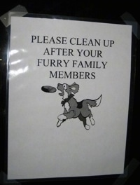 A sign with a dog jumping for a frisbee that says 'PLEASE CLEAN UP AFTER YOUR FURRY FAMILY MEMBERS