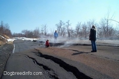 Three People standing on a steaming cracked road
