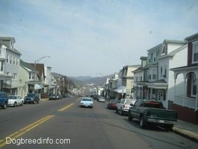 A picture of a neighboring coal town named Ashland with row homes of houses and cars on each side of the street