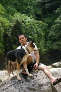 Hitman the Panda Shepherd and his owner is sitting on a rock