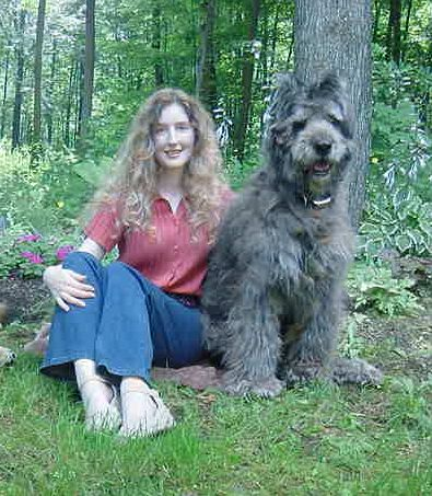 Dixie the Bouvier des Flandres sitting in the grass next to a lady with flowers and trees in the background