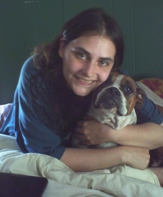 Baby Girl the Boxer being hugged by its owner in a bed