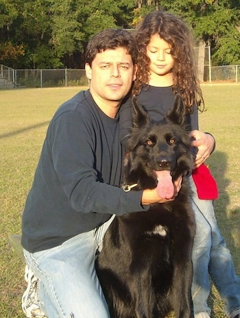 A black German Shepherd is sitting outside in the outfield of a baseball field in front of a man and a little girl who are both wearing blue shirts.