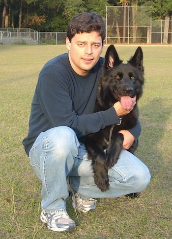 A man in a blue shirt has his arms wrapped around the body of a black German Shepherd in the outfield of a baseball field.
