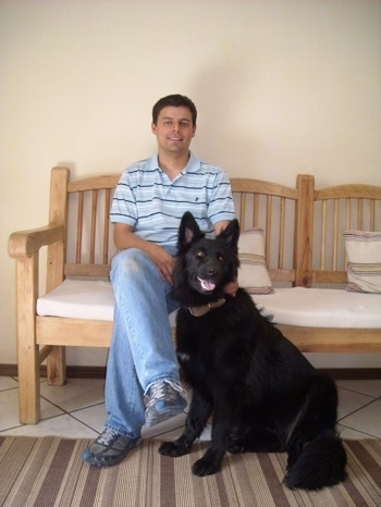 A man is sitting on a wooden bench inside of a room and there is a black German Shepherd sitting in front of it