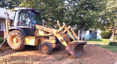 A yellow backhoe is on a mound of dirt in the front yard of a home.