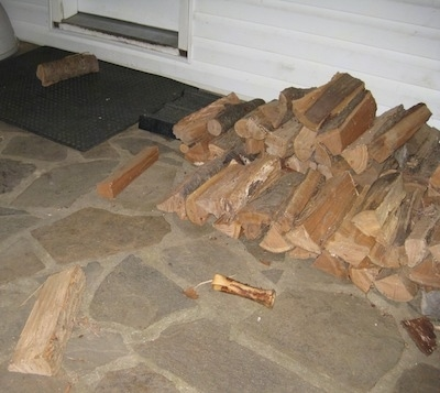 A stacked pile of split logs on a stone porch with a few logs separated from the pile and a dog bone laying in front of it in front of a white farm house.