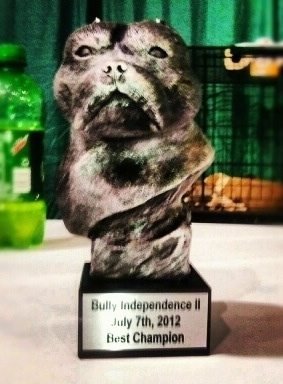 A trophy with the face of an American Bully on it. The plaque reads - Bully Independence II July 7th,2012 Best Champion.