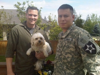 Riley the Cavachon is in the arm of a man who is standing next to another man in a US Army Uniform
