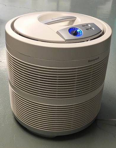 A white HEPA filter sitting on a gray floor against a white wall