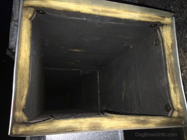 The inside of a fiberglass lined HVAC air duct that is very dirty and dry rotted.