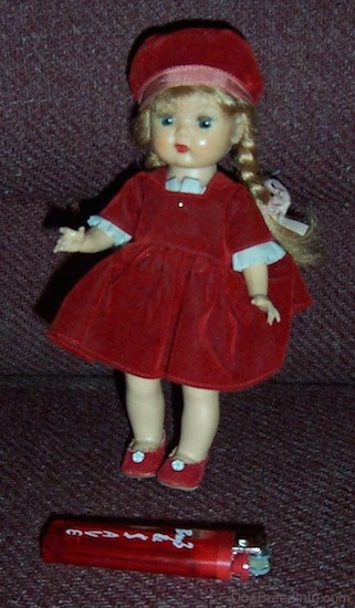 A small doll with long blonde braids wearing a red velvet hat and dress and red shoes standing up with a red lighter in front of her for size comparison.