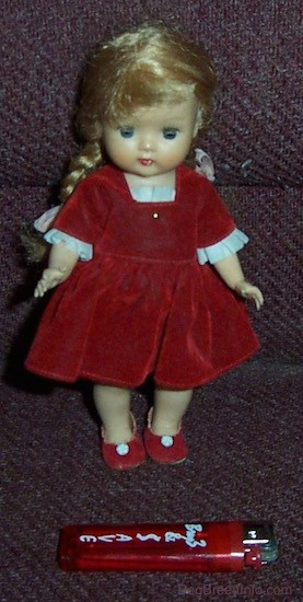 A small doll with long blonde braids wearing a red velvet dress and red shoes with small white flowers on them standing up with a red lighter in front of her for size comparison. The doll has blue eyes, a small nose and red lips.