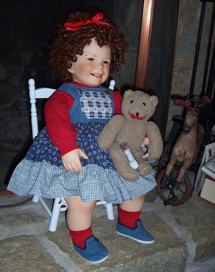 A realistic looking doll of a little girl with short curly ringlet curls in her hair, rosy cheeks, dark eyes, smiling with her teeth showing wearing a red ribbon in her hair, a red shirt and a blue jean colored dress, red socks and jean colored blue shoes holding a brown teddy bear with lip stick on its face and a tube of lip stick attached to the bear. The doll is sitting on a white wooden chair on a stone fireplace. There is a vintage rocking horse next to it.
