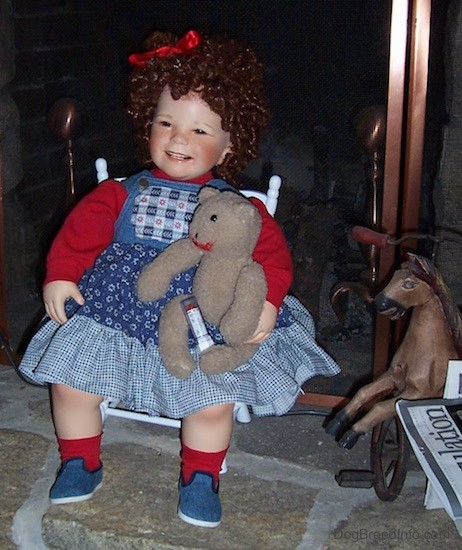 A doll that looks like a real little girl. She has Shirley Temple curly hair with a red ribbon on her head. Her cheeks are blush pink and her eyes are squinted and dark. She is smiling and her white teeth are showing. On her lap is a brown bear with red lip stick on its lips with a tube of lipstick attached to the bear. The doll has a red shirt, a blue jean dress, red socks and blue jean colored shoes and she is sitting in a white wooden chair in front of a stone fireplace with a vintage rocking  horse toy next to them.