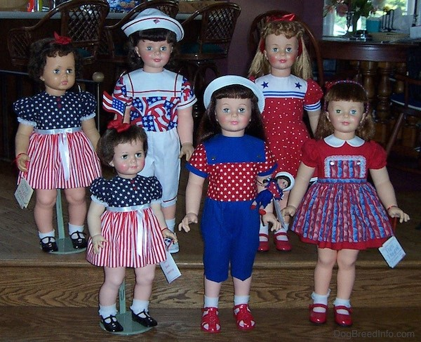 Front view - Six realistic looking large dolls dressed in red, white and blue standing on wooden steps. Two dolls have white hats and two dolls have red ribbons and two have red hair bands.