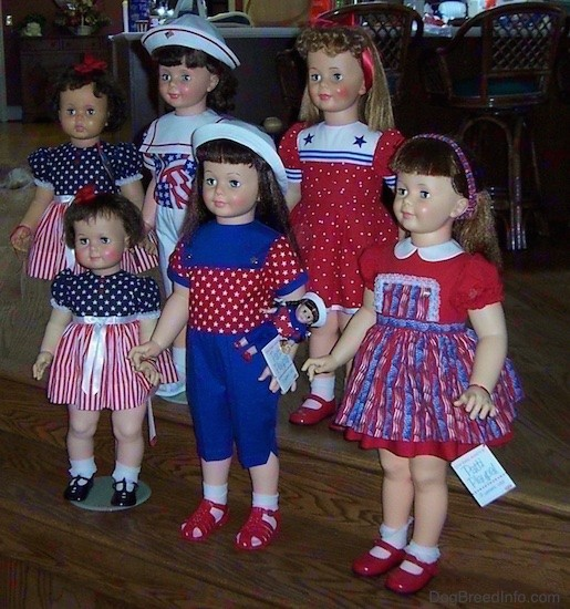 Side view - Six realistic looking large dolls dressed in red, white and blue standing on wooden steps. Three dolls have red shoes, two have black shoes and one has on white shoes. One larger doll wearing a white hat has a small identical toy doll attached to her shirt.