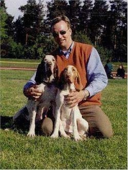 Two Bracco Italianos sitting in front of there owner who is kneeling on the grass and holding them close