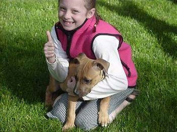 A girl is kneeling in grass wearing a hot pink vest and a white shirt and she has a tan Pit Bull puppy laying across her lap. She is giving a thumbs up, the puppy is looking to the left.