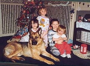 Four children are sitting together in pajamas in front of a Christmas tree with a black and tan German Shepherd dog that is laying down looking forward.
